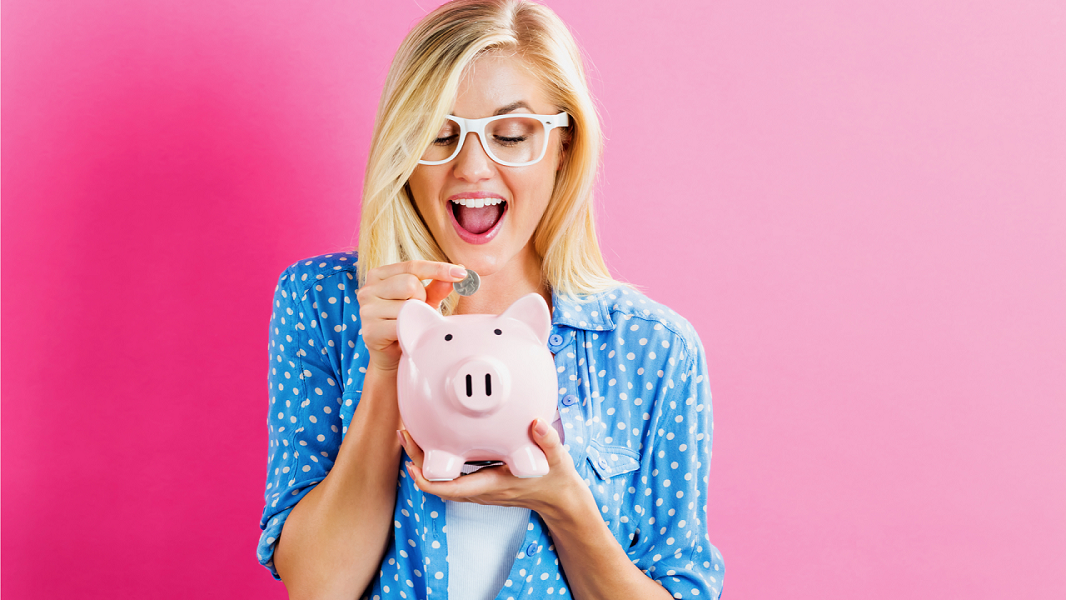Photo of woman putting money in piggy bank